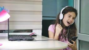 Baile del adolescente de la muchacha y canto en auriculares de la música la colegiala escucha la música en línea y baila y dentro almacen de metraje de vídeo