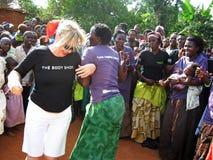 Baile del ayudante humanitario de la mujer africana y blanca para la alegría delante de los aldeanos Uganda África Fotos de archivo