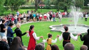 Baile del grupo de personas en el círculo, danzas tradicionales búlgaras, trajes nacionales del color almacen de video