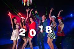 Baile del grupo de personas en el club de noche con la celebración de días festivos de la Navidad del sombrero de Papá Noel Foto de archivo libre de regalías