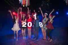 Baile del grupo de personas en el club de noche con la celebración de días festivos de la Navidad del sombrero de Papá Noel Fotos de archivo