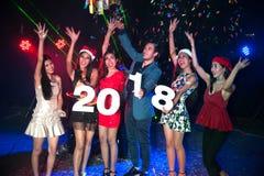 Baile del grupo de personas en el club de noche con la celebración de días festivos de la Navidad del sombrero de Papá Noel Foto de archivo