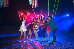 Baile del grupo de personas en el partido del club de noche y el fondo de las luces Fotografía de archivo libre de regalías