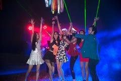 Baile del grupo de personas en el partido del club de noche y el fondo de las luces Foto de archivo libre de regalías