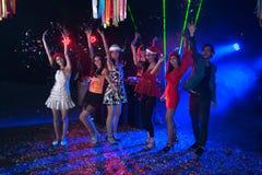 Baile del grupo de personas en el partido del club de noche y el fondo de las luces Imagen de archivo libre de regalías