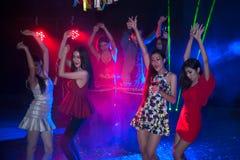 Baile del grupo de personas en el partido del club de noche y el fondo de las luces Imagen de archivo