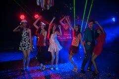 Baile del grupo de personas en el partido del club de noche y el fondo de las luces Fotos de archivo