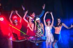 Baile del grupo de personas en el partido del club de noche y el fondo de las luces Imágenes de archivo libres de regalías