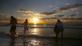 Baile del grupo de personas y diversión de salto el tener en el agua en la playa en la puesta del sol - cámara lenta metrajes