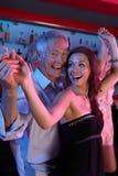 Baile del hombre mayor con una mujer más joven en barra ocupada Foto de archivo libre de regalías
