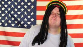 Baile del hombre y reggae rastafarian felices del canto en el fondo de una bandera de los E.E.U.U. almacen de metraje de vídeo