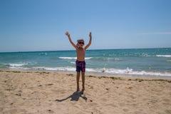 Baile del niño y salto en la playa imagenes de archivo