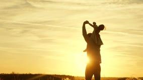 Baile del pap? en sus hombros con su hija en sol El padre viaja con el beb? en sus hombros en rayos de la puesta del sol A almacen de video