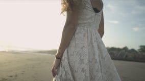 Baile despreocupado de la mujer en la puesta del sol en la playa
