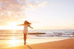 Baile despreocupado feliz de la mujer en la playa en la puesta del sol Imagen de archivo
