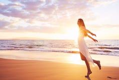 Baile despreocupado feliz de la mujer en la playa en la puesta del sol Imagen de archivo libre de regalías
