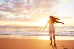 Baile despreocupado feliz de la mujer en la playa en la puesta del sol Fotografía de archivo