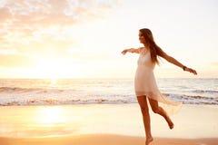Baile despreocupado feliz de la mujer en la playa en la puesta del sol Imágenes de archivo libres de regalías