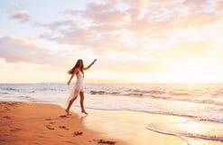 Baile despreocupado feliz de la mujer en la playa en la puesta del sol Foto de archivo