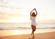 Baile despreocupado feliz de la mujer en la playa en la puesta del sol Imagenes de archivo