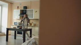 Baile divertido joven alegre de la mujer y canto con la cucharón mientras que mientras que cocina en la cocina en casa