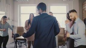 Baile ejecutivo afroamericano feliz con los colegas en las fiestas en la oficina casuales, celebrando el logro 4K del negocio almacen de video