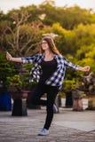 Baile emocionado de la muchacha y música que escucha con el teléfono elegante de los auriculares en la calle Foto de archivo libre de regalías