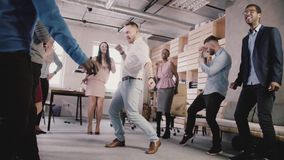 Baile europeo feliz del hombre de negocios con los colegas en círculo en teambuilding la cámara lenta del partido corporativo de  almacen de metraje de vídeo