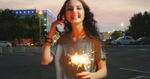 Baile feliz de la muchacha de la cámara lenta con el sparcler en puesta del sol de la ciudad almacen de metraje de vídeo