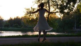 Baile feliz de la mujer en parque en la puesta del sol almacen de video