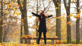 Baile feliz de la mujer en parque y hojas amarillas que lanzan en aire almacen de metraje de vídeo