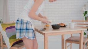 Baile feliz de la mujer joven en pijamas que llevan de la cocina por mañana La muchacha escucha música en smartphone, prepara el  foto de archivo