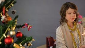 Baile feliz de la niña con la bengala cerca del árbol de navidad en casa, celebración almacen de metraje de vídeo