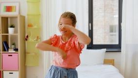 Baile feliz de la niña en su sitio en casa almacen de metraje de vídeo