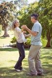 Baile feliz de los pares en el parque Imagen de archivo libre de regalías