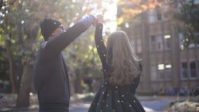 Baile feliz de los pares en el parque del otoño almacen de metraje de vídeo