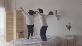 Baile feliz de los pares en la cama en el cuarto en casa o el hotel junto Mujer joven que salta y que hace girar alrededor feliz metrajes