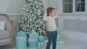 Baile feliz del niño pequeño al lado del árbol de navidad y de los presentes almacen de metraje de vídeo