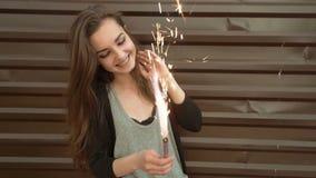 Baile feliz emocional joven de la mujer con la bengala del fuego en sus manos, mirando alegre en calle de la ciudad por la tarde metrajes
