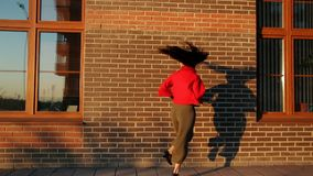 Baile feliz joven artístico de la mujer en la calle almacen de metraje de vídeo