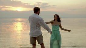Baile feliz joven de los pares en la playa en la puesta del sol Concepto de amor almacen de video