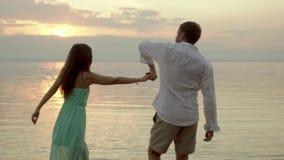 Baile feliz joven de los pares en la playa en la puesta del sol Concepto de amor almacen de metraje de vídeo