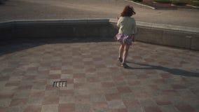 Baile feliz loco de la chica joven en una chaqueta y una falda viva colorida - bailarina del biege de la fuente vacía del palaci metrajes