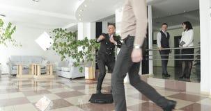 Baile feliz loco del hombre de negocios en el traje que lleva del pasillo corporativo que celebra el logro almacen de video