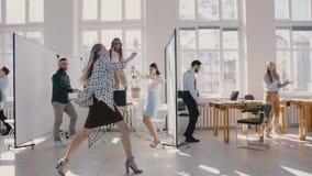 Baile femenino caucásico feliz joven del jefe en la oficina moderna que celebra así como la cámara lenta de los colegas multi metrajes