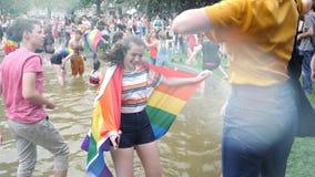 Baile gay feliz de la mujer de la muchedumbre de LGBT que lleva la bandera del orgullo gay almacen de video