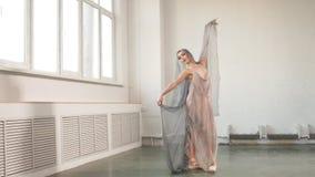 Baile hermoso de la bailarina con un velo que vuela aislado en blanco metrajes