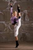 Baile hermoso de la muchacha del salto de la cadera sobre la pared gris Fotos de archivo