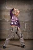 Baile hermoso de la muchacha del salto de la cadera sobre la pared gris Imagen de archivo libre de regalías