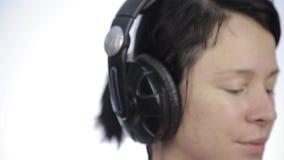 Baile hermoso de la mujer en auriculares mientras que escucha una música en un fondo ligero almacen de metraje de vídeo